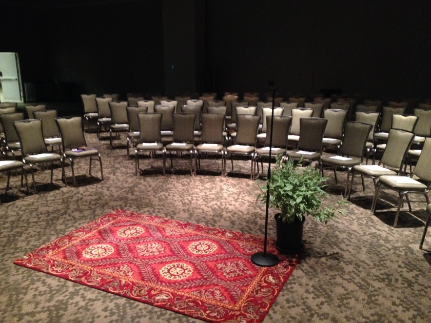 A big room can still feel like a stage with a little light control, oval seating... and a rug and plant.