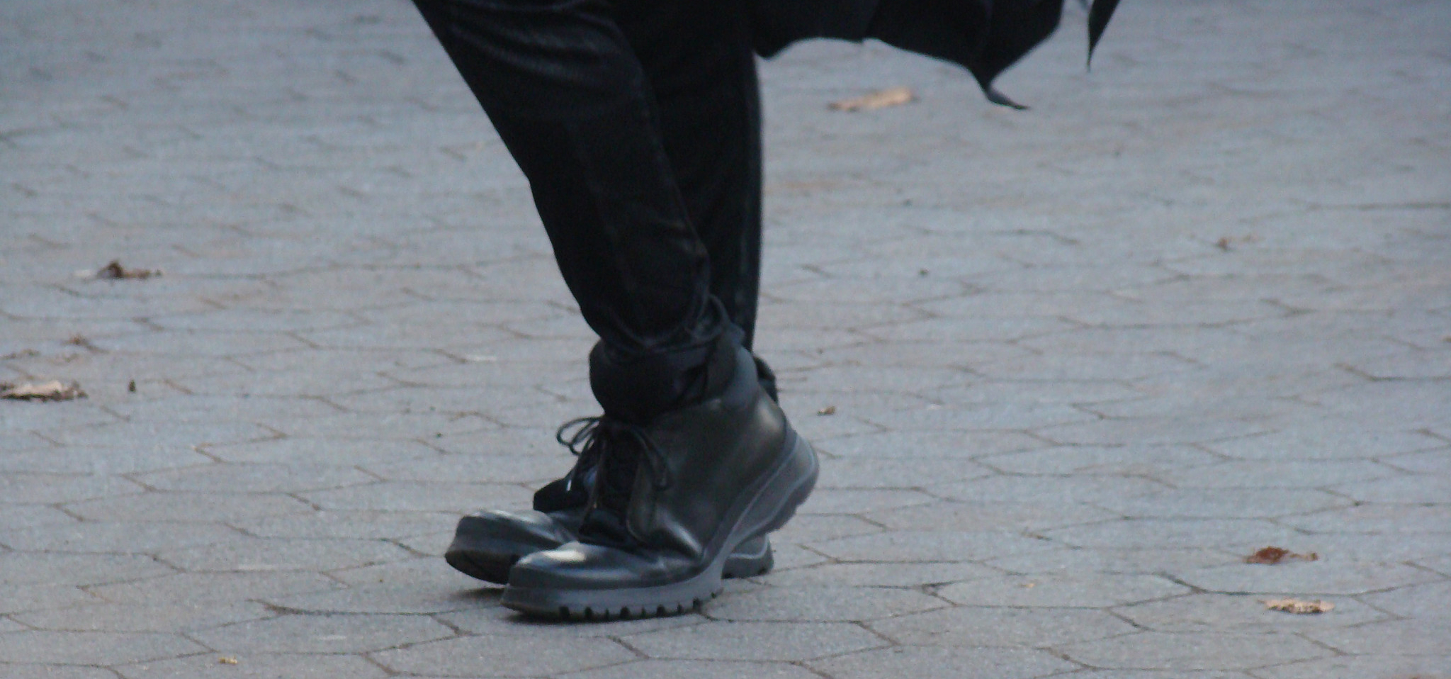 close up of legs and feet of person in Batman costume doing the Moon walk dance.